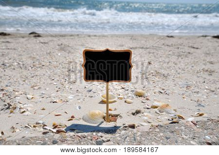 Empty black wooden plaque on the seashore