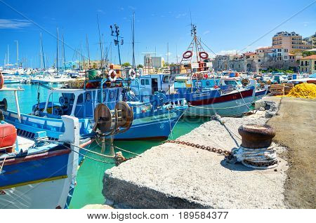 CRETE ISLAND GREECE SEP 12 2012: View on beautiful classic old piscatory small sea boats ships white yachts Greek Heraklion sea port tourists and blue water of Aegean Sea bay. MSC cruises