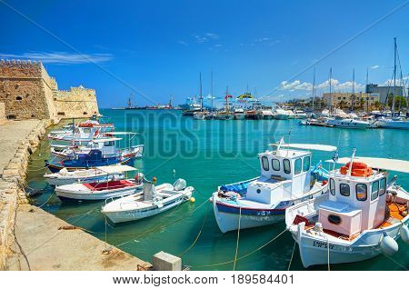 CRETE ISLAND, GREECE, SEP 12, 2012: View on beautiful classic old piscatory small sea boats ships, white yachts, Greek Heraklion sea port, tourists, and blue water of Aegean Sea bay. MSC cruises
