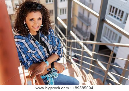 Portrait of happy mulatto girl listening to music while standing on stairs outside the building. She is looking at camera and smiling
