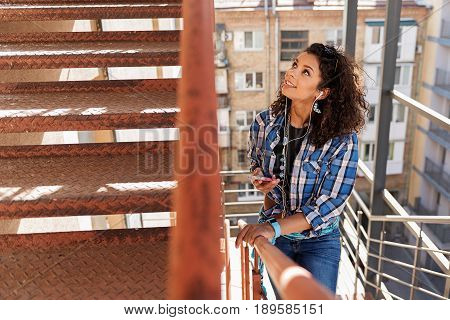Curious mulatto girl is going upstairs and looking up with interest. She is holding smartphone and smiling
