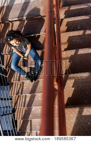 Relaxed mulatto girl is enjoying sunshine on her face. She is sitting on staircase with closed eyes. Top view