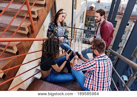Cheerful friends are hanging out on staircase. They are talking and laughing. Guy and girl are using smartphones