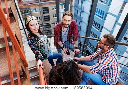 Joyful young man and woman are hanging out with their friends. They are standing on stairs and smiling while looking at camera with happiness. Portrait