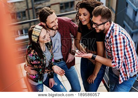 Carefree young men and women are enjoying communication on staircase. They are laughing