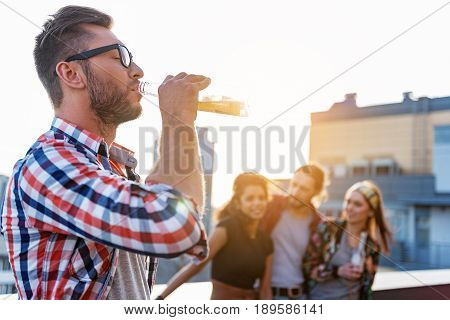Thirsty young man is drinking cold beer on party. He is standing on roof with closed eyes. His friends are standing and laughing on background