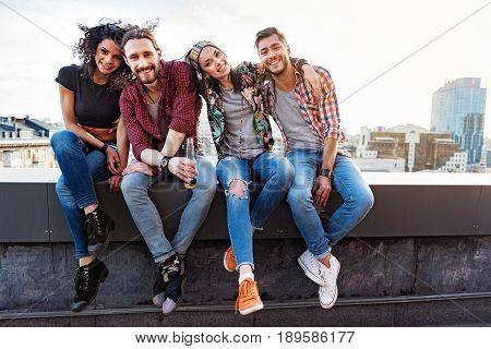 Portrait of happy young friends hanging out on roof. They are sitting on border and embracing. Men and women are looking at camera and smiling
