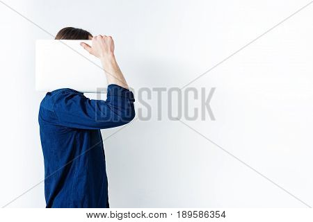 Young man is standing and holding white laptop on his shoulder while covering his face by gadget. Isolated and copy space in right side