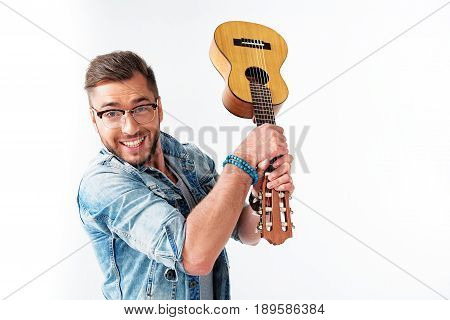 Ready to break this guitar. Portrait of joyful young male guitarist is raising musical instrument and looking at camera with passion. He is standing and smiling. Isolated and copy space