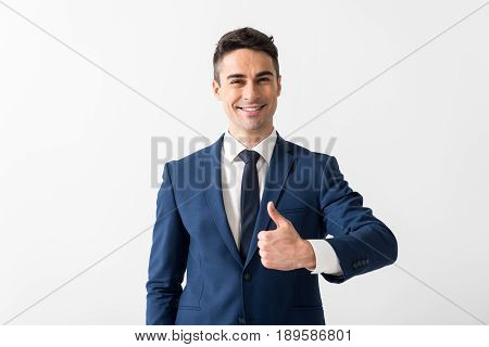 Everything is good. I like my job. Portrait of cheerful young man demonstrating thumb up gesture. Isolated
