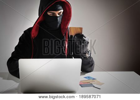 Restrained hacker stealing money from credit card with laptop. He looking at it while locating at desk. Copy space
