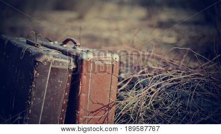 Two old shabby suitcases stand forgotten on the road in a faded grass.