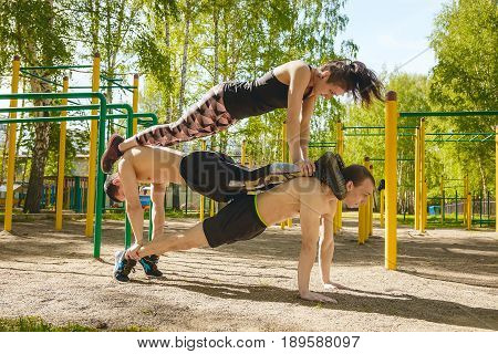 Fitness mans and woman exercising outdoors in the Park. Street workout