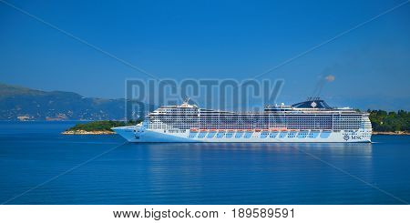 CORFU ISLAND, GREECE, JUN,06, 2014: View on giant amazing white touristic passenger liner in Ionian Sea. MSC FANTASIA cruise liners. Cruise ship Greece islands holidays tours Mediterranean Sea cruises