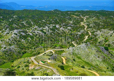 Beautiful view on Corfu island green hills mountains and automobile car road highway spiral to Monastery of Pantokrator. Greece holidays vacation tourist tour. Green hills mountains road way path