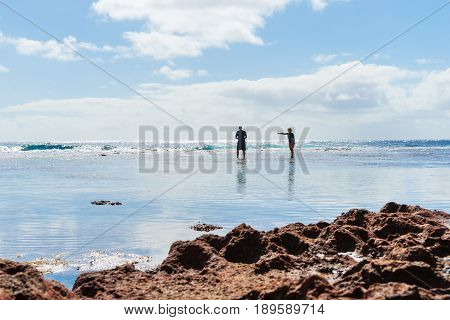Niue, South Pacific - May 25, 2017;  Two figures silhouetted exploring rock pools on coral shelf on tropical Niue