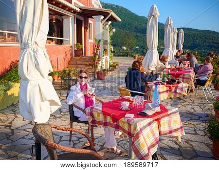 CORFU ISLAND, GREECE, JUNE 03, 2014: Young pretty woman is having dinner in classical Greek taverna restaurant cafe. Tourists and guests in Taverna Sun set. Greece islands holidays vacation tours
