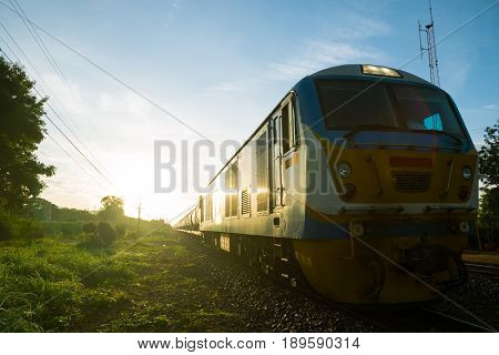 Running Old Train on Railway Track in morning sunshine with Rural Scene