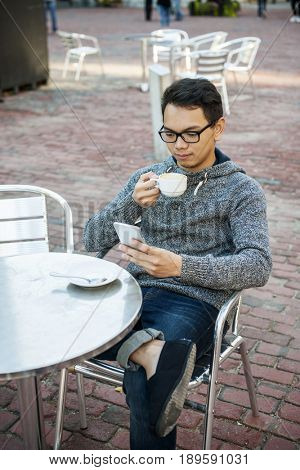 Serious young asian man sitting in relaxing outdoor cafe holding cup of coffee and using mobile phone