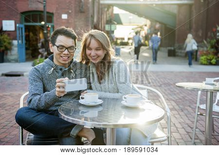 Two smiling young people looking into smartphone while sitting at a table in outdoor cafe