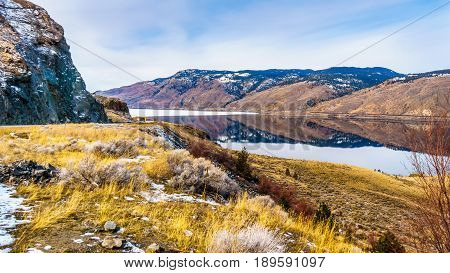 Kamloops Lake, which is a very wide portion of the Thompson River, on a cold winter day with the surrounding mountain reflecting in the quiet surface of the lake