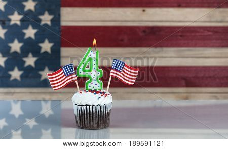 Chocolate cupcake and number four candle and small USA flags with rustic wooden United States Flag in background. July 4th holiday concept.