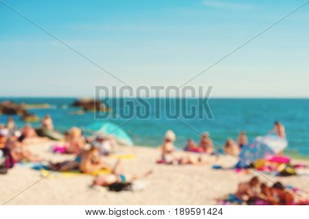Intentionally out of focus image of people relaxing and having fun at a beach with colorful sun umbrellas