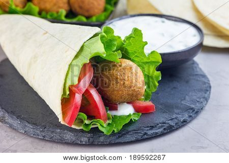 Chickpea falafel balls with vegetables and white sauce roll sandwich preparation horizontal copy space