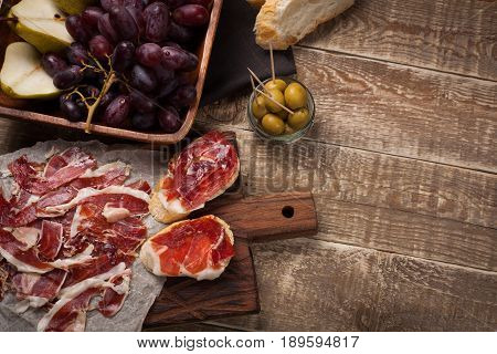 Jamon Iberico with white bread, olives on toothpicks and fruit on a wooden background. Top view with copy space.