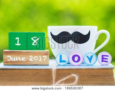 Father's day concept. stack of books gifts tea cup with black Mustache and flower on background