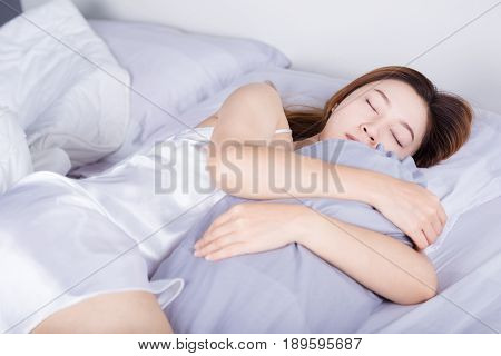 Woman Sleeping With Bolster Pillow On Bed In Bedroom