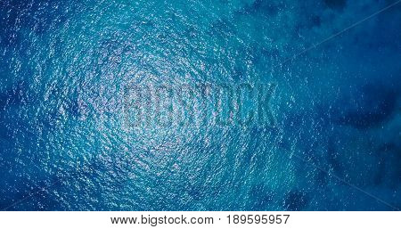 Aerial flying drone view of Maldives white sandy beach abstract waves water surface texture on sunny tropical paradise island with aqua blue sky sea ocean 4k.