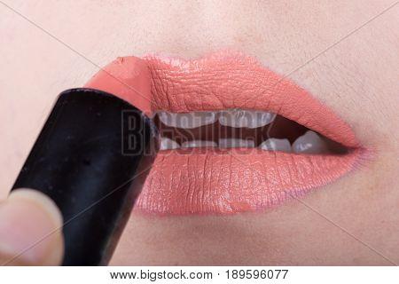 Woman Applying Orange Lipstick On Her Lips