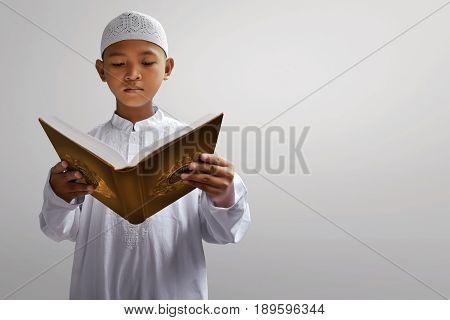 Asian muslim kid reading koran with gray background