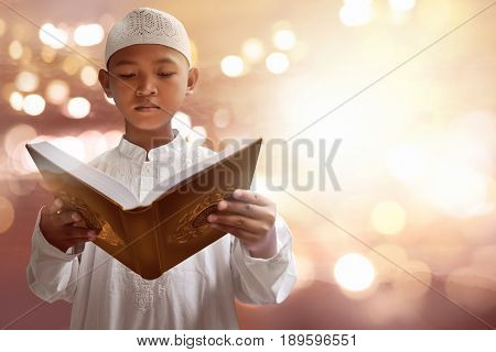 Asian muslim kid reading koran with bokeh background