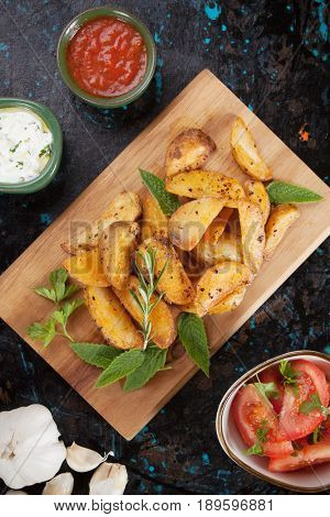 Spicy roasted potato wedges with herbs and dips