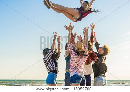 Group of hipster young friends on beach together tossing up a girl. Freedom and frienship concept