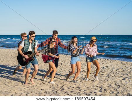 Party on the beach with guitar. Friends dancing together at the beach. Happy youth time