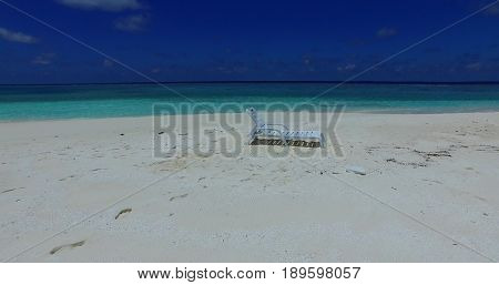 Maldives white sandy beach sunbed on sunny tropical paradise island with aqua blue sky sea water ocean 4k