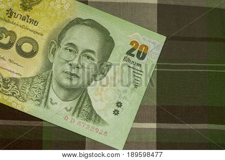 Close up of Thai banknote Thai bath with the image of Thai King. Thai banknote of 20 Thai baht on Green Scottish fabric. Thai currency concepts., Sensitive Focus.