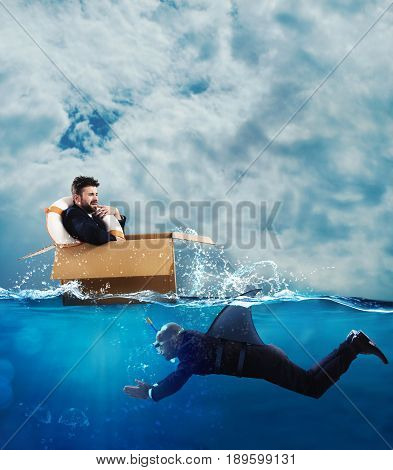 Fearful Businessman on cardboard while businessman with fin shark swims under water