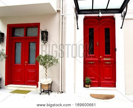 Two, bright red, vinatge doors next to each other.