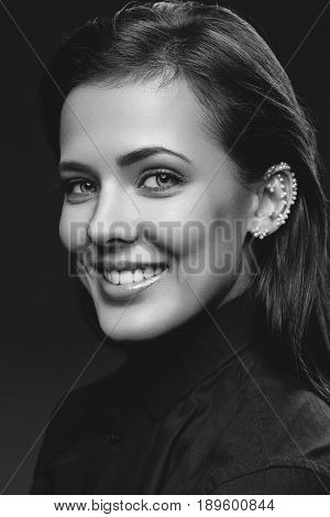 Beautiful young happy woman with natural make up and pearls glued on ear wearing black shirt. Beauty shot on black background. Copy space. Monochrome.