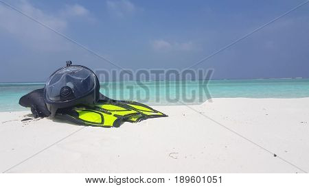 Maldives white sandy beach snorkeling fins mask flippers scuba on sunny tropical paradise island with aqua blue sky sea water ocean 4k