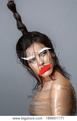 Beautiful young woman with odd fancy hairstyle, body wrapped in plastic foil and eyebrows and lips paper cutouts on face. Beauty shot on grey background. Copy space.