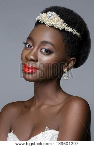 Beautiful black skin young woman with red lips in white gown and pearl tiara. Beauty shot on grey background. Copy space.