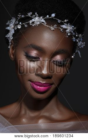Beautiful young black woman with perfect skin and pink tone make up. Bride with crystal wreath on head. Beauty shot on black background.
