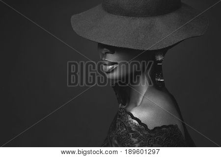Beautiful young African woman wearing large black hat. Beauty portrait on purple background. Copy space. Monochrome.