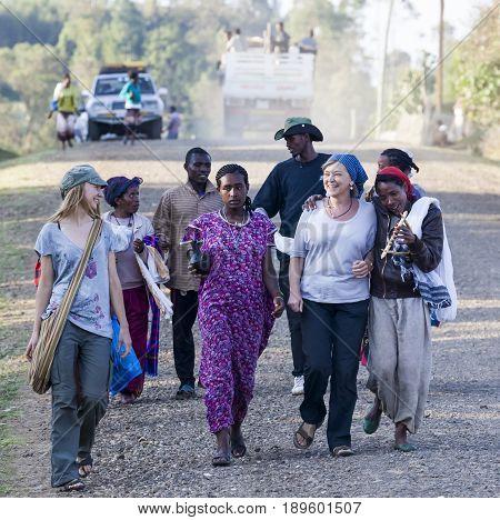 Western Tourists Surrounded By Local Dorze People. Hayzo Village. Dorze. Ethiopia.