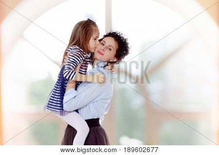 Happy young beautiful mother, lifted his little beloved daughter .And the girl kisses his mother on the cheek.In a room with a large semi-circular window.